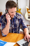 Handsome older man on call at music studio Stock Images