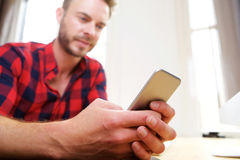 Handsome older man holding cellphone in hands at desk Royalty Free Stock Photography