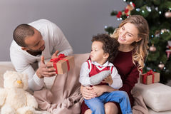 Handsome optimistic man holding a gift box. Present to my son. Handsome positive delighted men standing behind the sofa and looking at his son while holding a royalty free stock photo