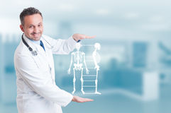 Handsome orthopedist doctor holding skeleton model hologram on h. Is hands and smiling as healthy bone concept with copyspace royalty free stock photography