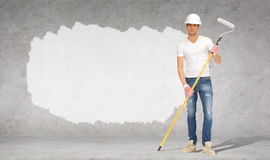 Handsome painter in helmet with paint roller Stock Photography