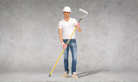 Handsome painter in helmet with paint roller Royalty Free Stock Images