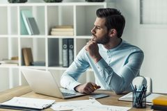 Handsome businessman working. Handsome pensive businessman is looking away and thinking while working with the laptop in the office Stock Image