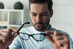 Handsome businessman working. Handsome pensive businessman is looking at his eyeglasses and thinking while working in the office Stock Image