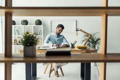 Handsome businessman working. Handsome pensive businessman is making notes while working in the office, view through the shelf Royalty Free Stock Image