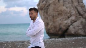 Young pensive guy walks along the seashore. Handsome bearded man spends time in thought outdoors. Cyprus. Paphos stock footage