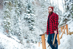 Handsome pensive man with axe standing in mountain winter forest Royalty Free Stock Image