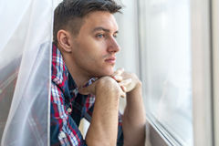 Handsome pensive man guy watching through the Royalty Free Stock Image