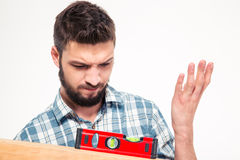 Handsome pensive young man measuring with spirit level Royalty Free Stock Image