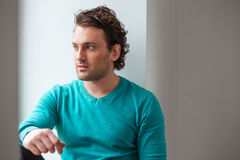 Handsome pensive young man sitting and looking at the window Royalty Free Stock Images