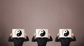 Handsome people in formal gesturing with yin yang sign on cardbo Royalty Free Stock Images