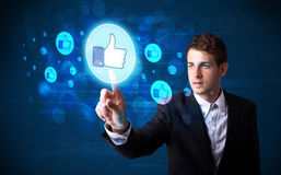 Handsome person pressing thumbs up button on modern social netwo Stock Photo