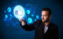 Handsome person pressing thumbs up button on modern social netwo Stock Photography