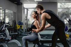 Handsome personal instructor helping his female client to training with dumbbells. Handsome personal instructor helping his female client to training with royalty free stock photos