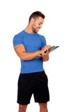 Handsome personal trainer with a clipboard. Isolated on a white background Stock Photos