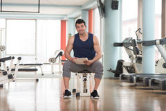 Handsome Personal Trainer With A Clipboard. Personal Trainer Takes Notes On Clipboard In a Gym Stock Photos