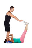 Handsome personal trainer helping a girl in her training. On white background Stock Images