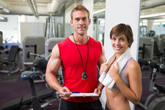Handsome personal trainer with his client smiling at camera Stock Photos