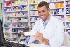 Handsome pharmacist scanning medicine box Royalty Free Stock Photo