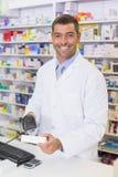 Handsome pharmacist scanning medicine box Stock Photos