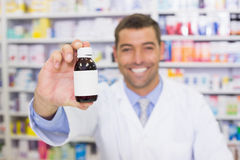 Handsome pharmacist showing medicine bottle Stock Photography