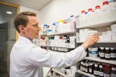 Handsome pharmacist taking medicine from shelf Stock Photography