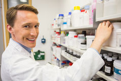 Handsome pharmacist taking medicine from shelf Royalty Free Stock Photos