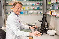 Handsome pharmacist using the computer Royalty Free Stock Images