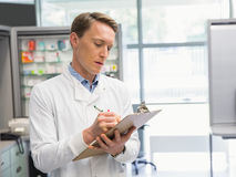 Handsome pharmacist writing on clipboard Royalty Free Stock Photography