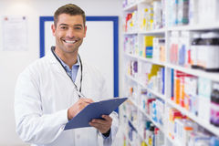 Handsome pharmacist writing on clipboard Stock Photos