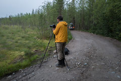 Handsome Photografer is making photos  on the forest road Royalty Free Stock Images
