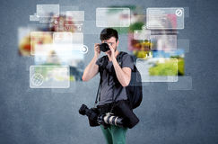 Handsome photographer with camera. A young professional male photographer holding cameras and taking pictures in front of a blue wall with pictures, icons, text Stock Image