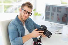 Handsome photographer holding his camera smiling at camera Royalty Free Stock Photography