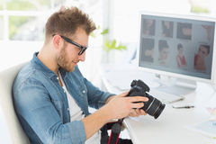 Handsome photographer looking at his camera Stock Images