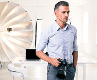 Handsome photographer standing with camera Stock Photos
