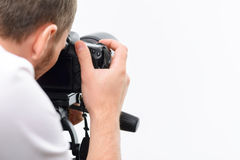 Handsome photographer working with professional. Shooting procedure. Young professional photographer uses his camera to make accurate frame stock photos
