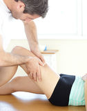 Handsome physical therapist giving a leg massage Royalty Free Stock Photography