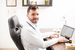 Handsome physician working on a laptop Royalty Free Stock Photography