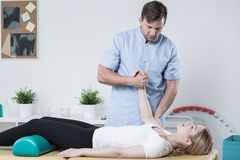 Handsome physiotherapist working with patient Royalty Free Stock Photography