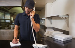 Handsome pizza delivery man taking an order over the phone Royalty Free Stock Photos