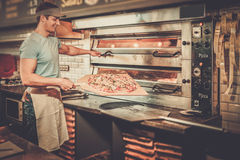 Handsome pizzaiolo making pizza at kitchen in  pizzeria. Stock Images