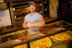 Handsome pizzaiolo making pizza at kitchen Royalty Free Stock Photography
