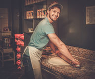 Handsome pizzaiolo rolling dough with  rolling-pin. Stock Photo