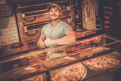Handsome pizzaiolo standing at kitchen in  pizzeria. Stock Photography