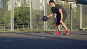 Handsome player playing basketball at the open air stock video