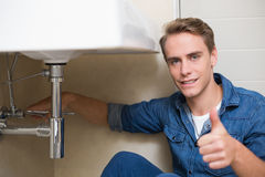 Handsome plumber gesturing thumbs up besides washbasin drain Royalty Free Stock Image