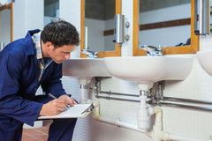 Handsome plumber looking at sink holding clipboard Royalty Free Stock Photography