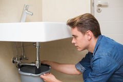 Handsome plumber repairing the drain of sink Stock Photo