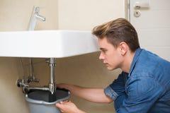 Handsome plumber repairing the drain of sink Stock Photo