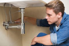 Handsome plumber repairing washbasin drain in bathroom Stock Images